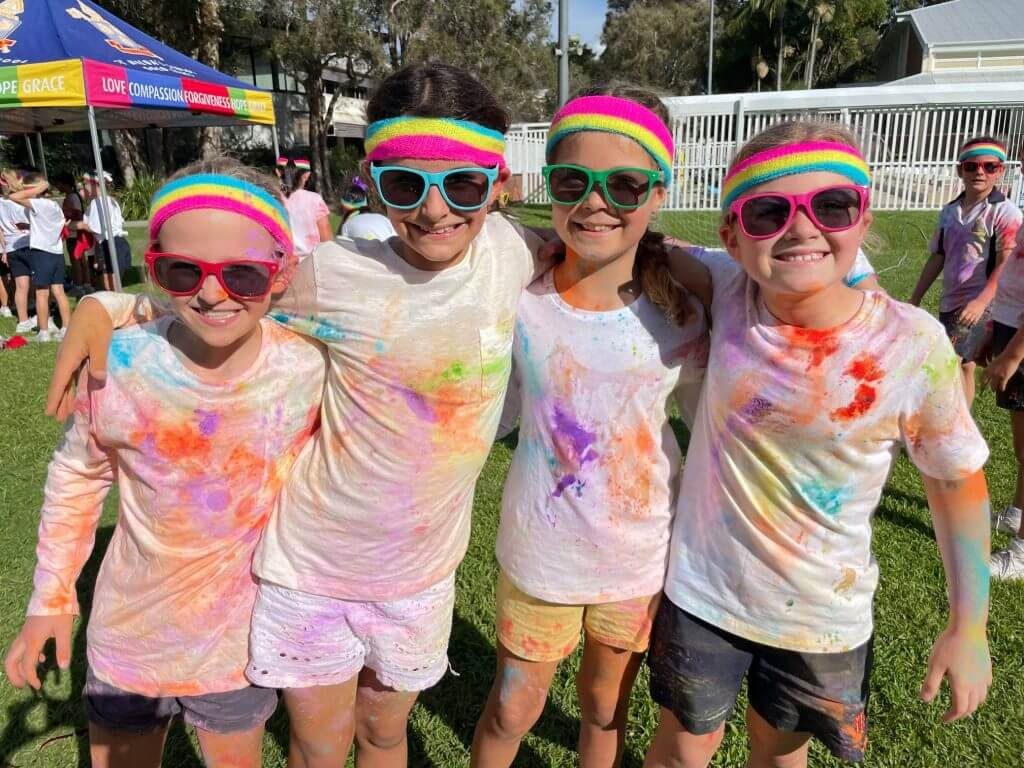 Students standing together smiling. They are covered in colour powder./