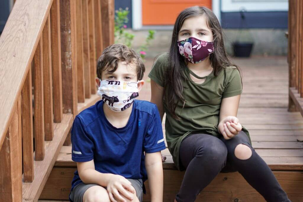 Kids sit on steps with masks to protect from COVID-19
